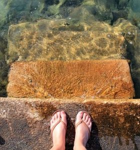 A pair of feet wearing sandals by the sea